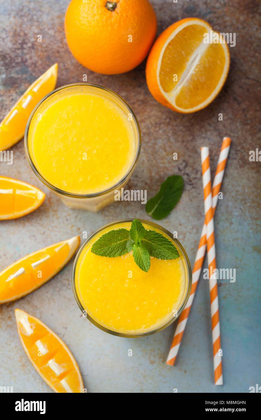 Dos vasos de zumo de naranja recién exprimido y menta sobre un fondo azul oxidado viejo. Vista superior Imagen De Stock