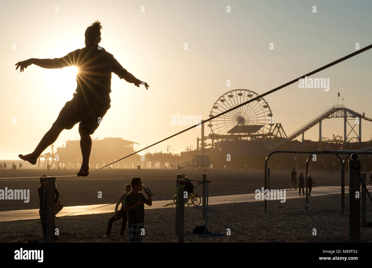 El hombre practicando en la cuerda floja en la playa cerca del embarcadero de Santa Mónica, Los Angeles, CA Imagen De Stock