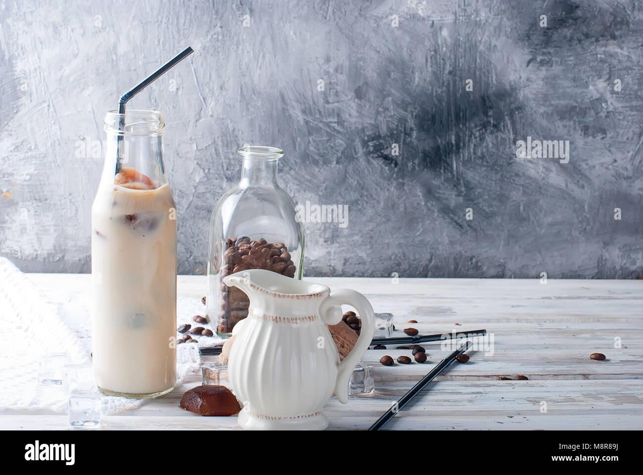 Café hielo en botella, mostachones, trozos de chocolate y granos de café en una mesa oscura Imagen De Stock