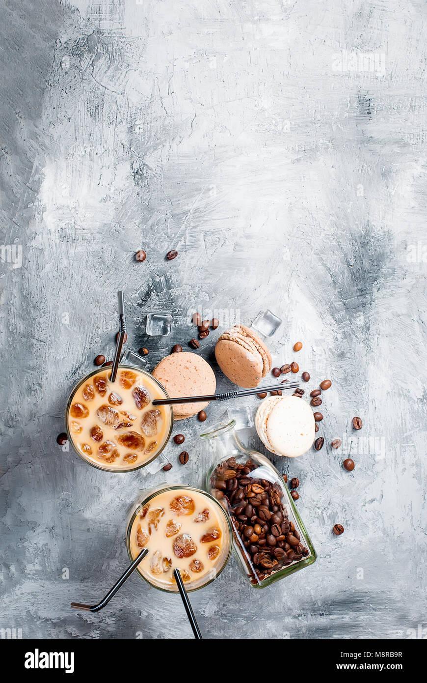 Café en cristal de hielo, mostachones, trozos de chocolate y granos de café en un cuadro gris , vista Imagen De Stock
