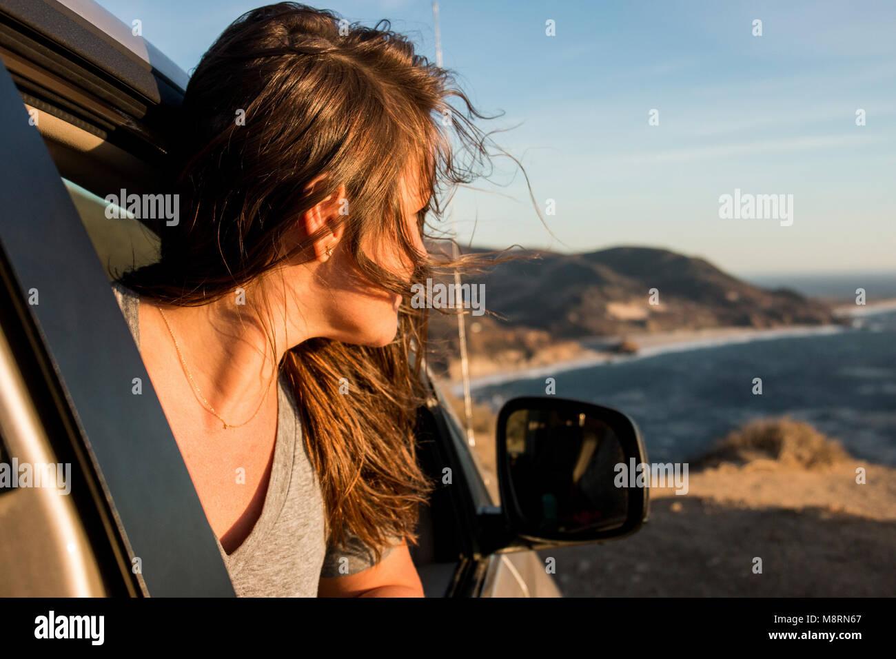Mujer mirando a través de ventanilla en la playa contra el cielo durante la puesta de sol Imagen De Stock