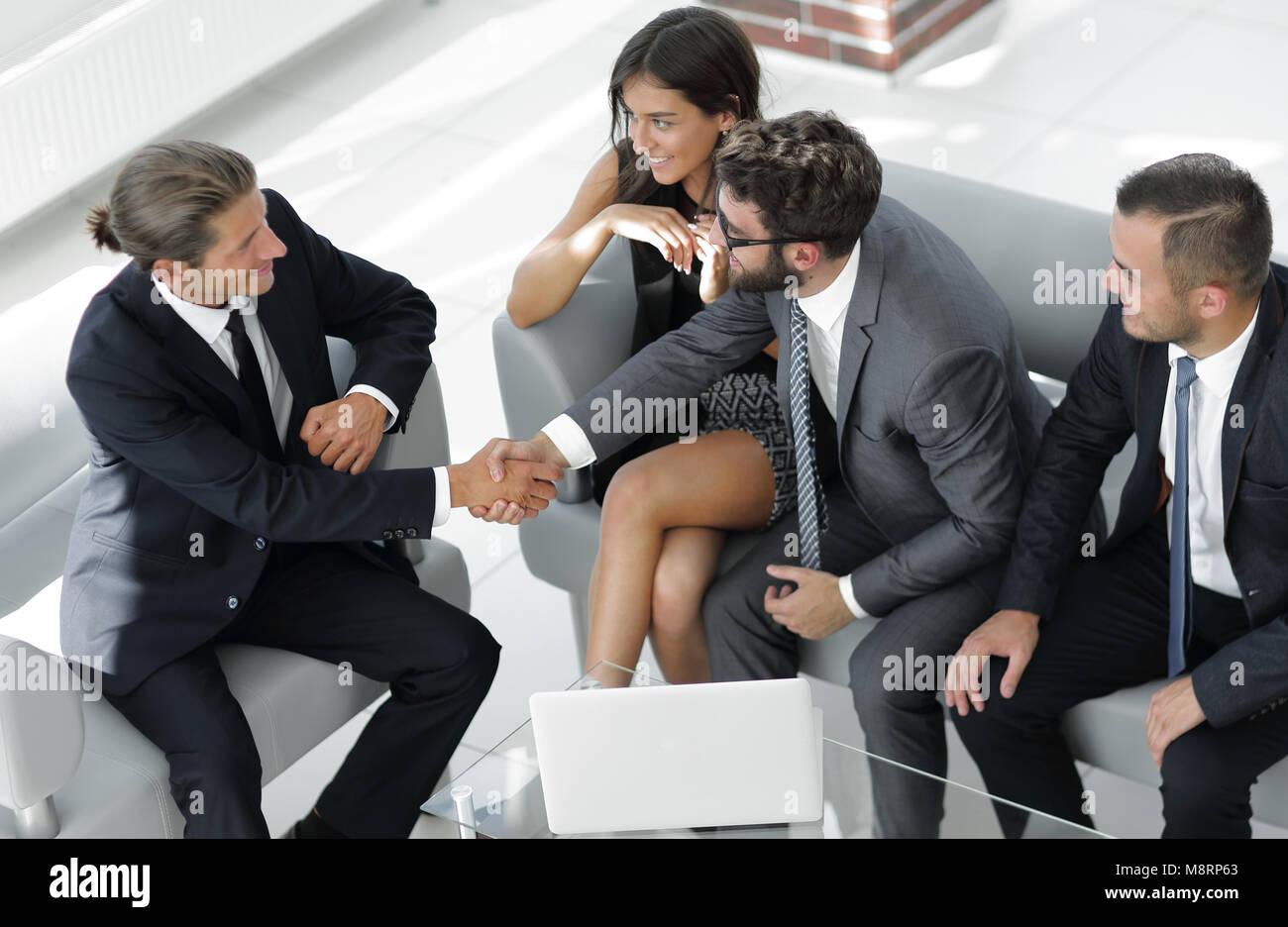 Apretón de manos Manager y el cliente sentado en el vestíbulo de la oficina. Imagen De Stock