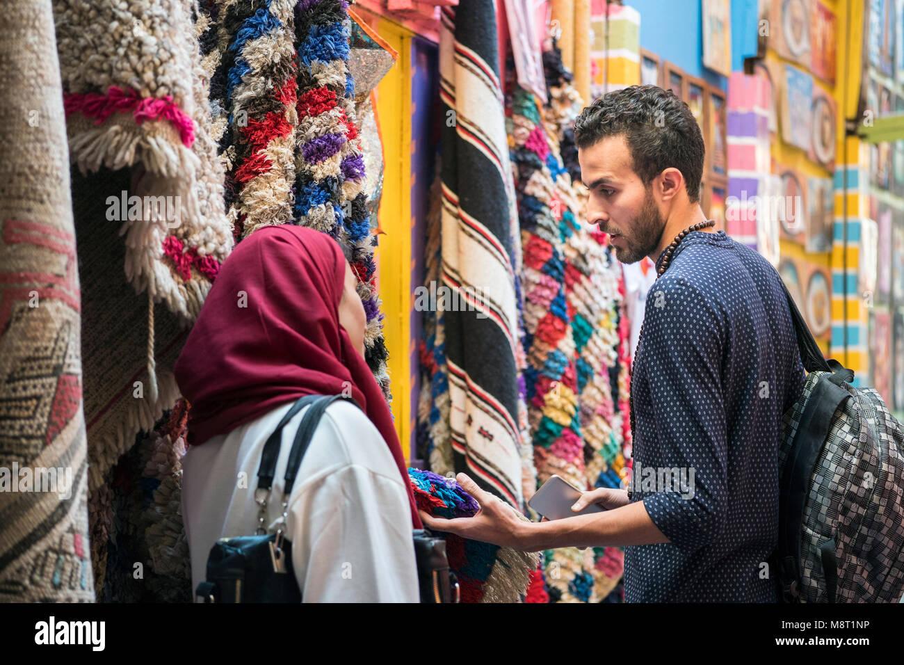 Sonriente joven pareja musulmana shopping y mirar las alfombras en un almacén textil Imagen De Stock