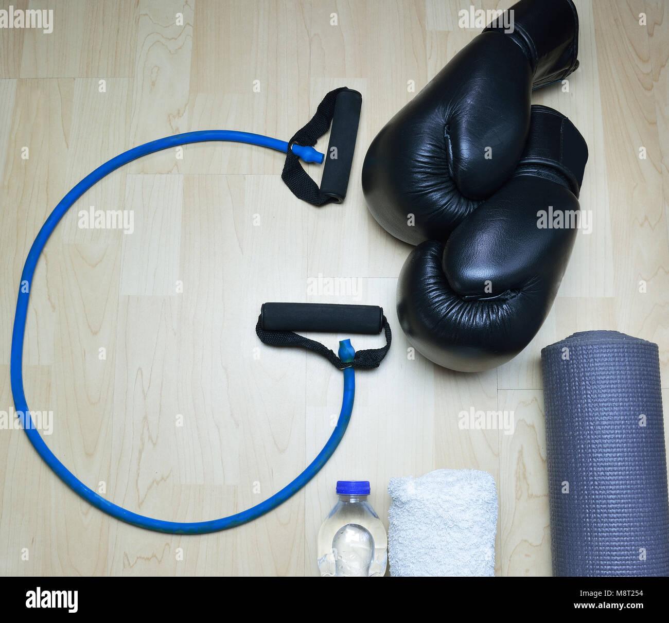 La cuerda en forma G , kick boxing guantes, botella de agua, toalla y rollable colchón sobre fondo de madera Imagen De Stock