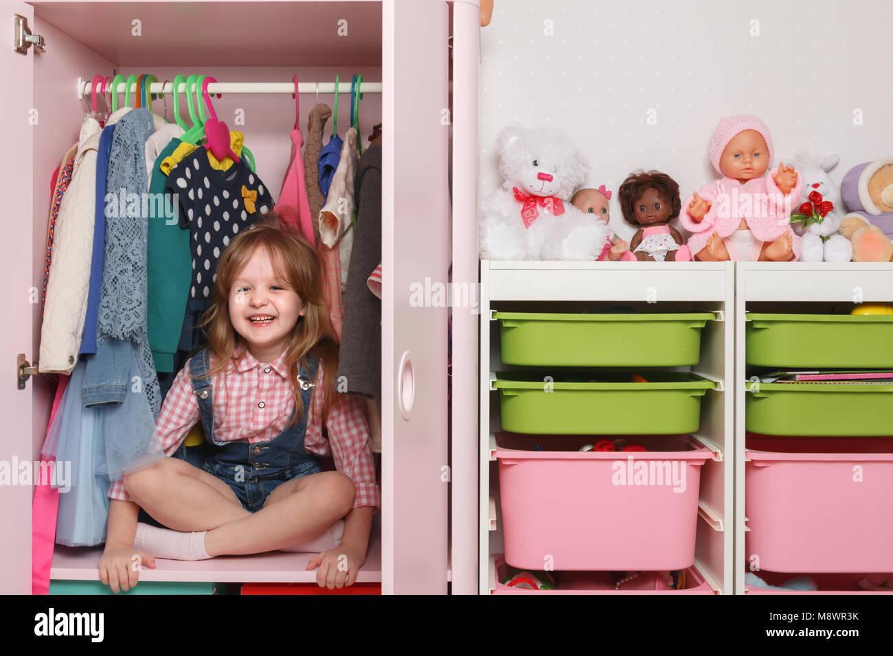 Una niña pequeña está sentada en un armario con un departamento de niños. Sistema de almacenamiento Imagen De Stock