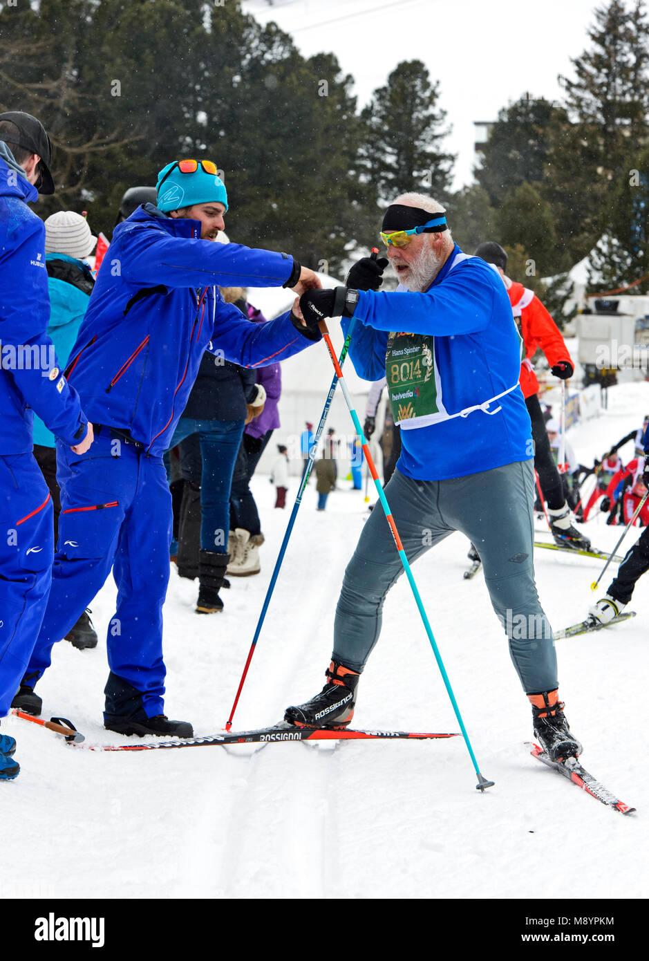 Esquiador de fondo con un palo roto se da asistencia, Engadin Skimarathon, 11 de marzo de 2018, San Moritz, Suiza Foto de stock