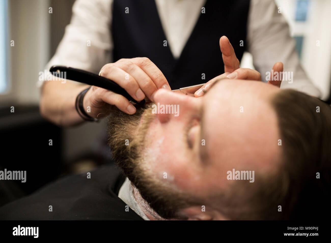 Retrato del hombre barbado siendo afeitado por el barbero Foto de stock