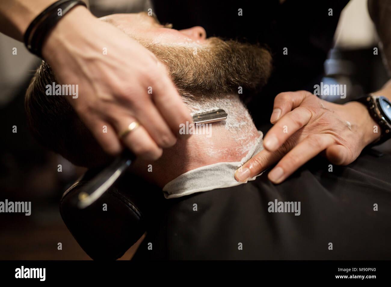 Retrato del hombre barbado siendo afeitado con maquinilla de afeitar Foto de stock