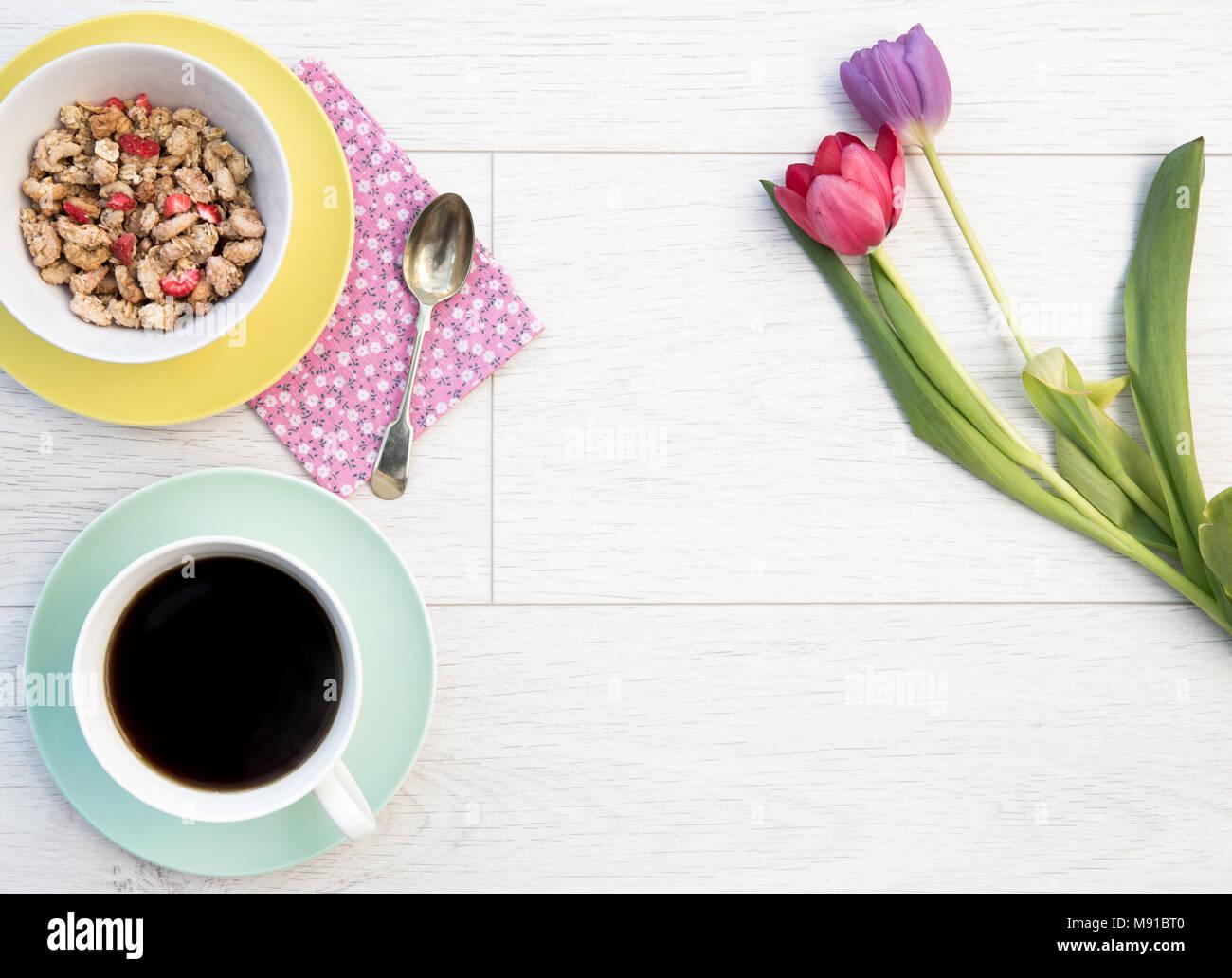 Mirando hacia abajo desde arriba en una mesa de madera blanca, con un desayuno femenino de muesli y café junto con los tulipanes, flores y copie el espacio. Foto de stock