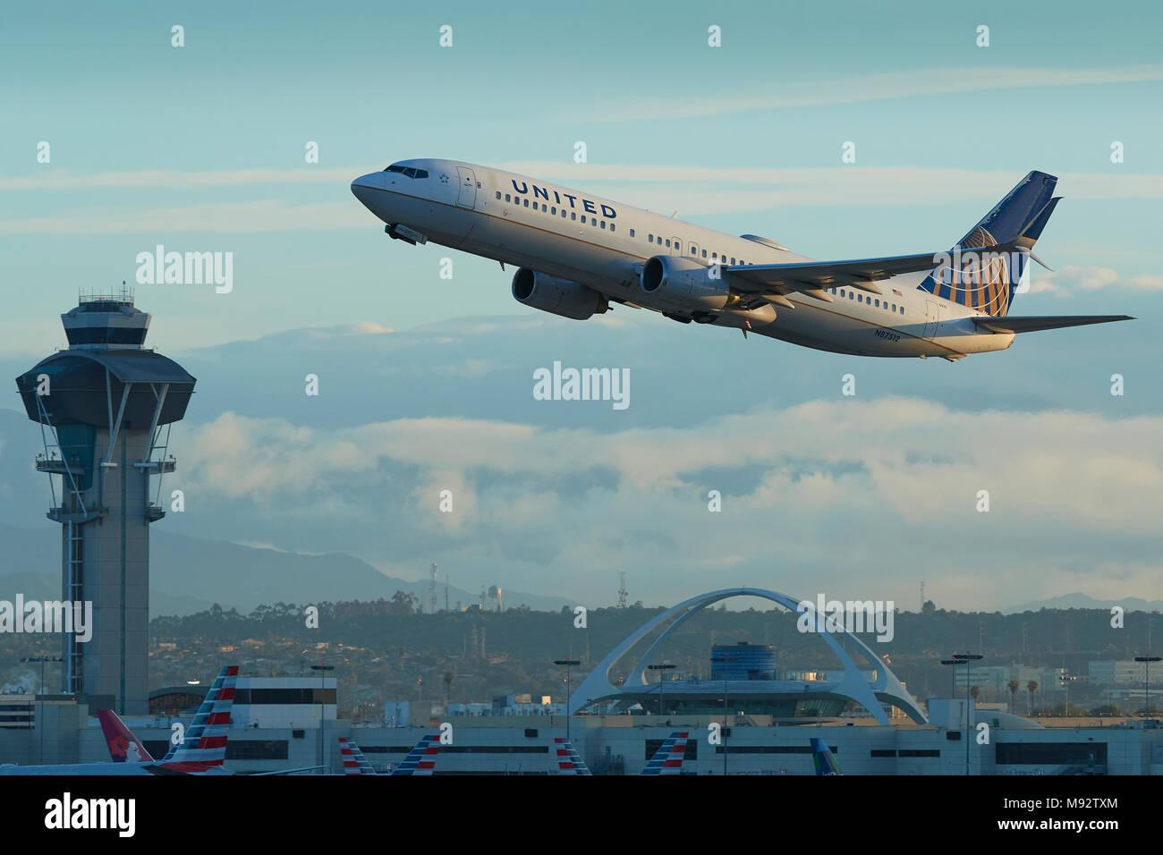 United Airlines Boeing 737-900 avión jet despegando desde el Aeropuerto Internacional de Los Angeles, LAX. El tema de la Torre de Control y edificio detrás. Foto de stock
