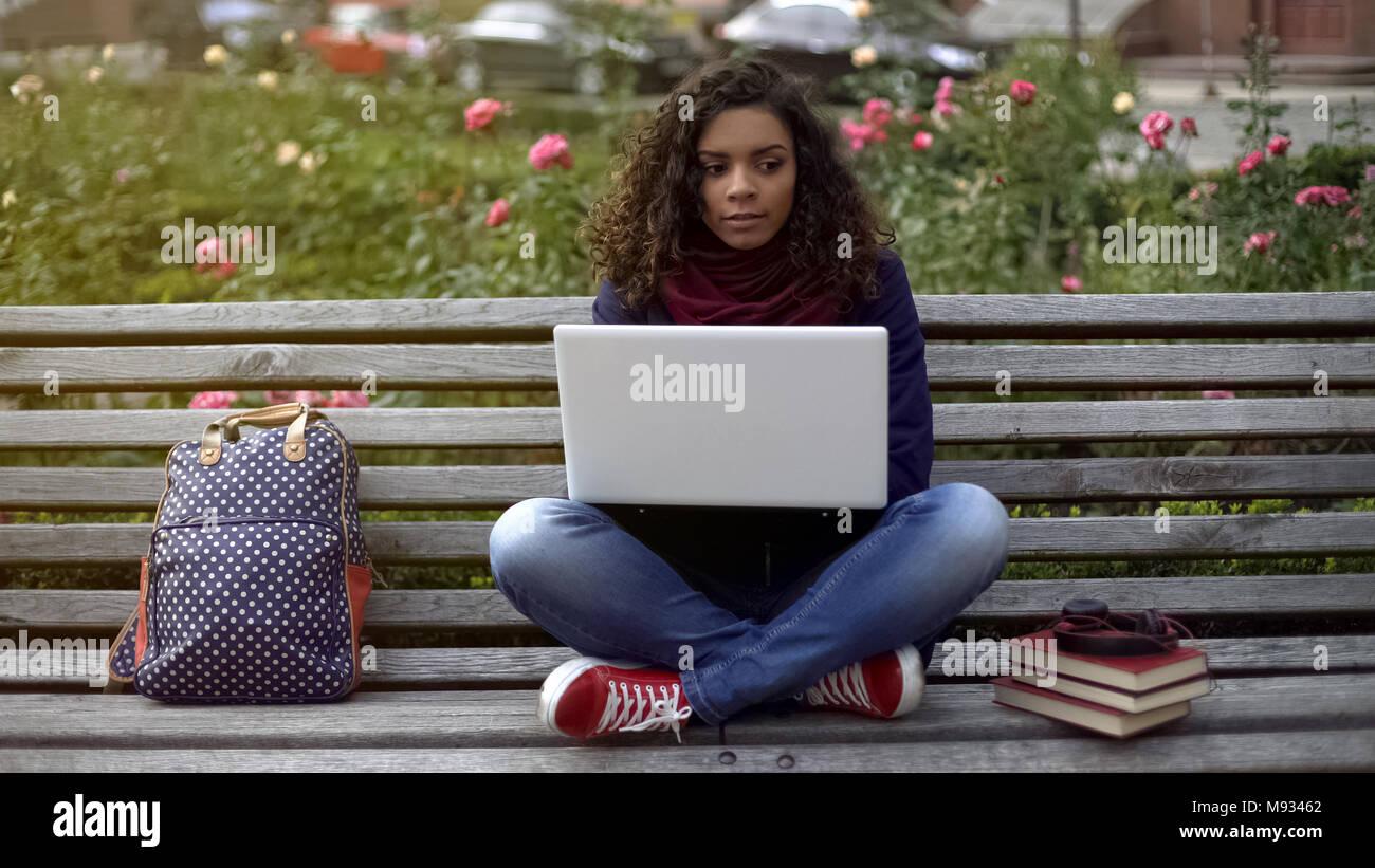 Atractivo de pelo rizado señora sentada en un banco, pensando en su proyecto de trabajo Foto de stock