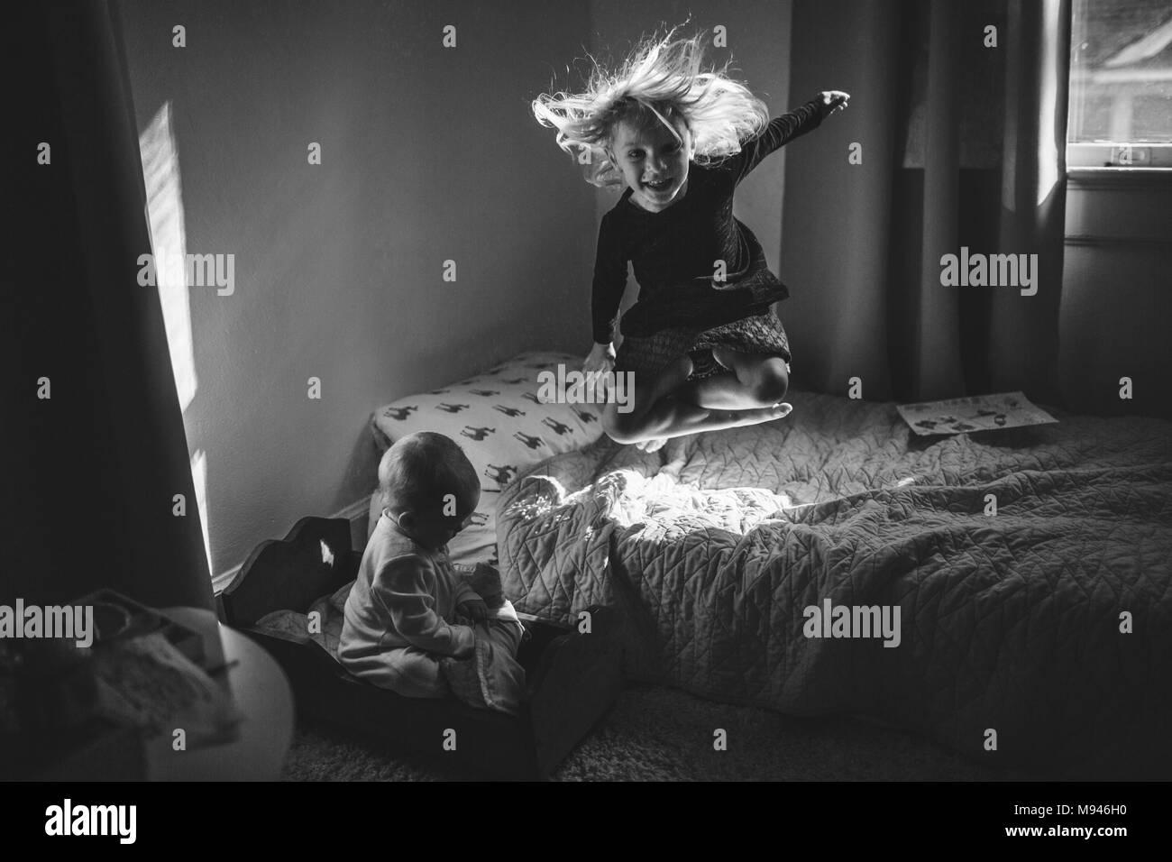Chica saltando en la cama con su bebé junto a ella Imagen De Stock