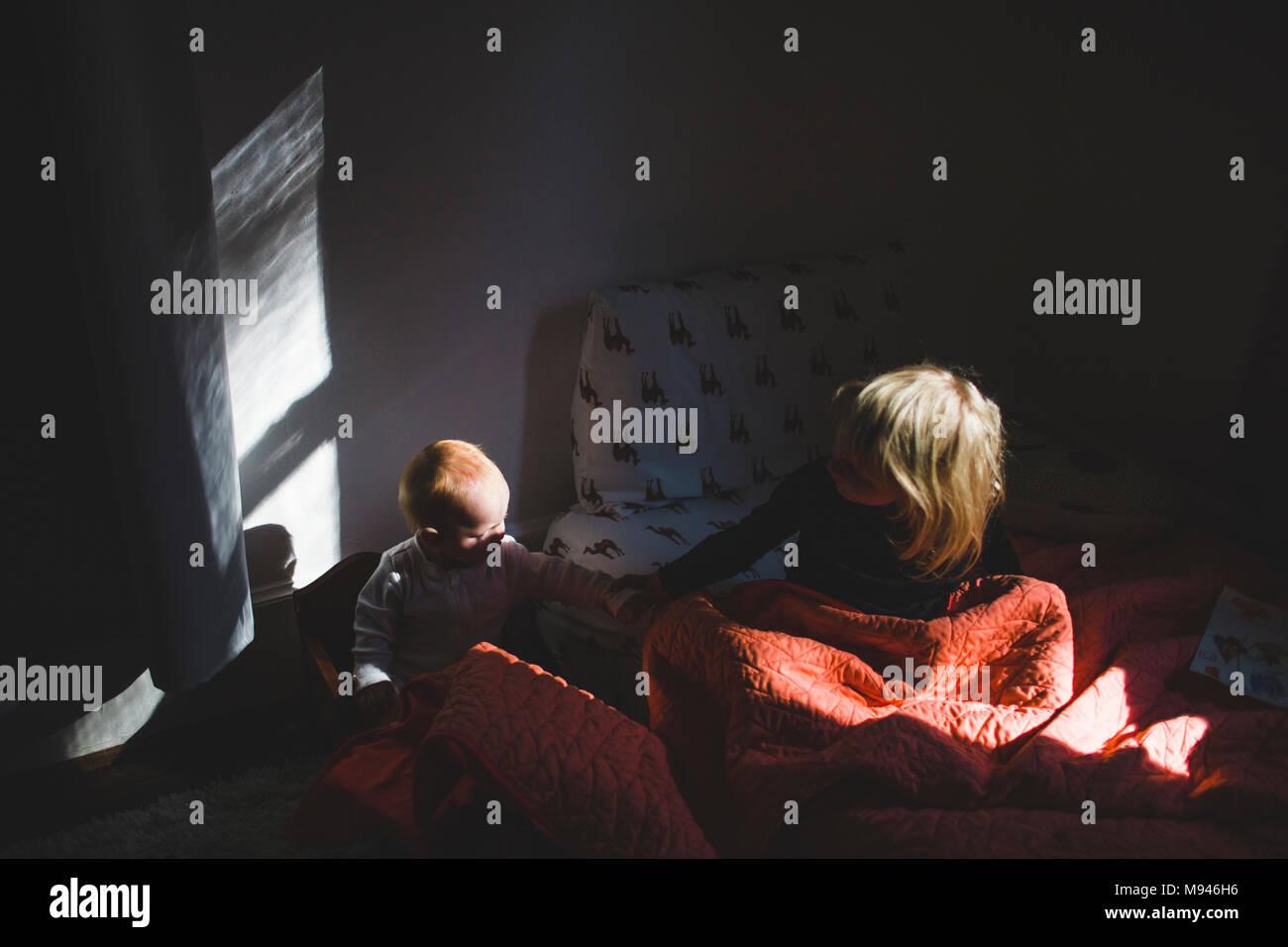 Niña y Bebe aguantando mutuamente en camas separadas Imagen De Stock