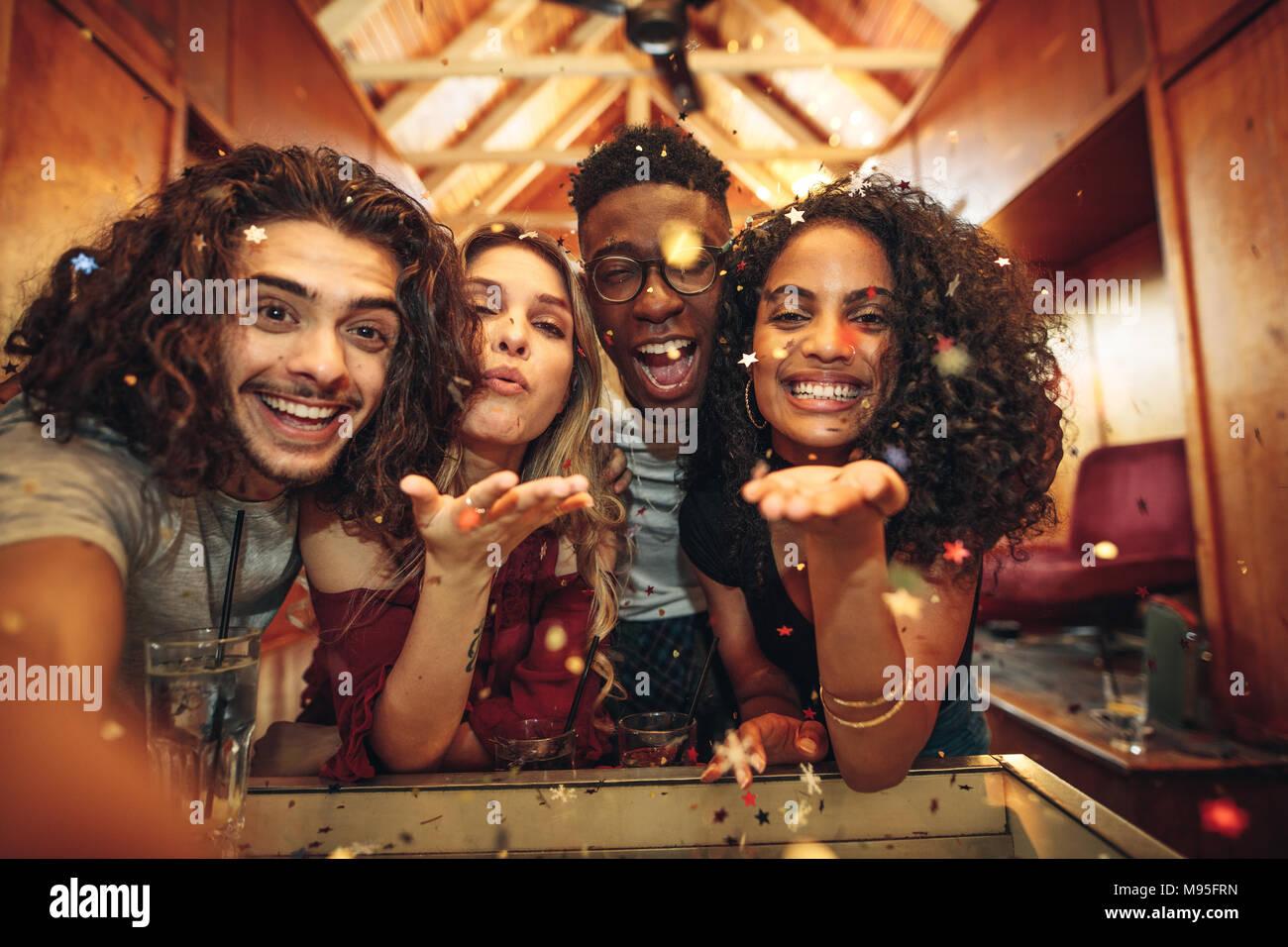 Grupo de amigos disfrutando de un partido y soplando confetti. Hombres y mujeres capturar la diversión en selfie en discoteca. Imagen De Stock