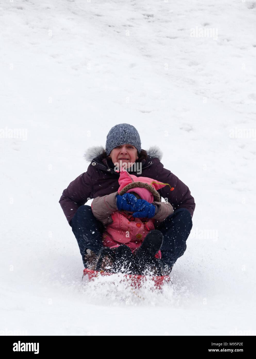 Abuela parece asustado y nieta cubre sus ojos mientras trineo en Quebec, Canadá Imagen De Stock
