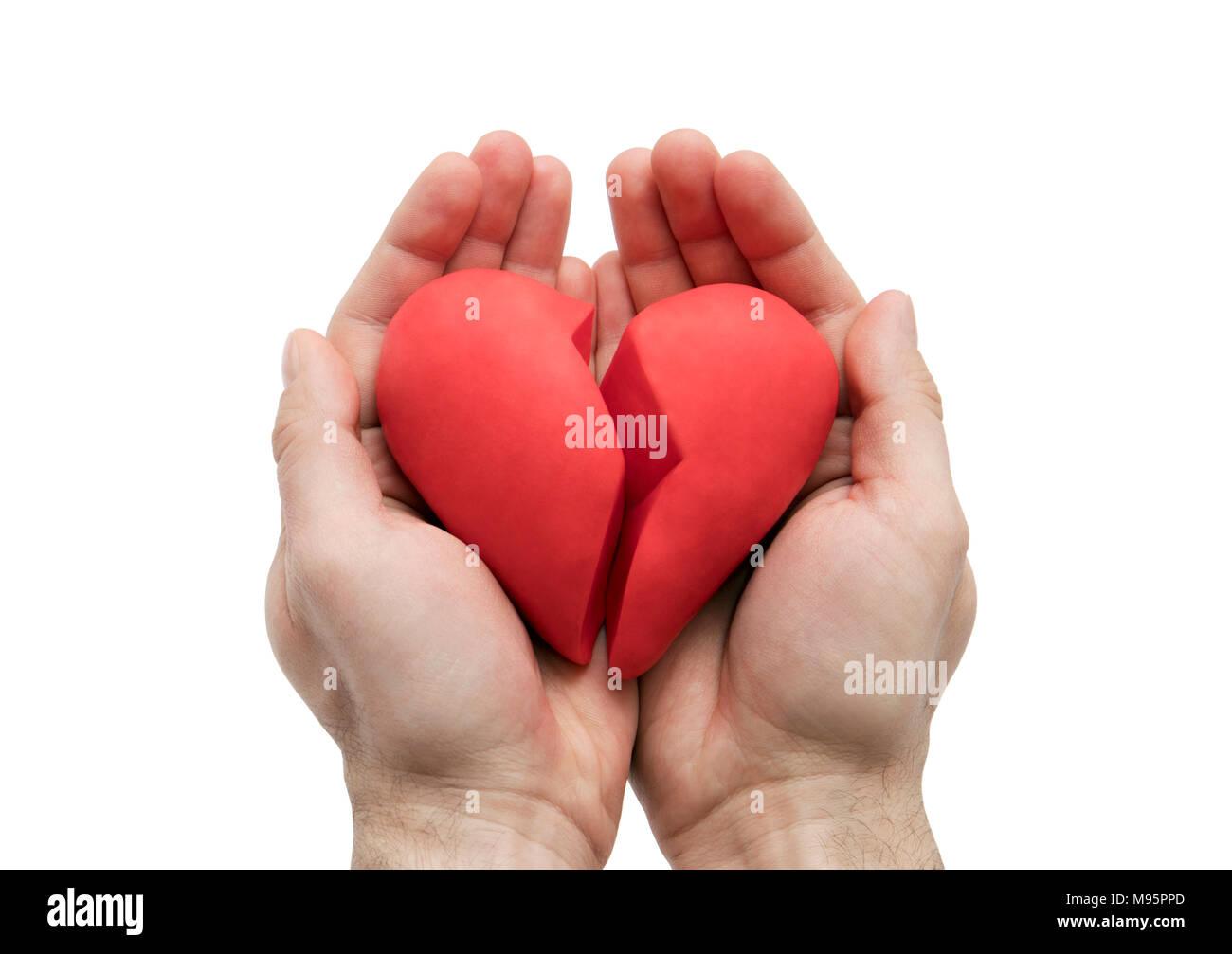 Corazón roto en manos aislado en blanco con trazado de recorte Imagen De Stock