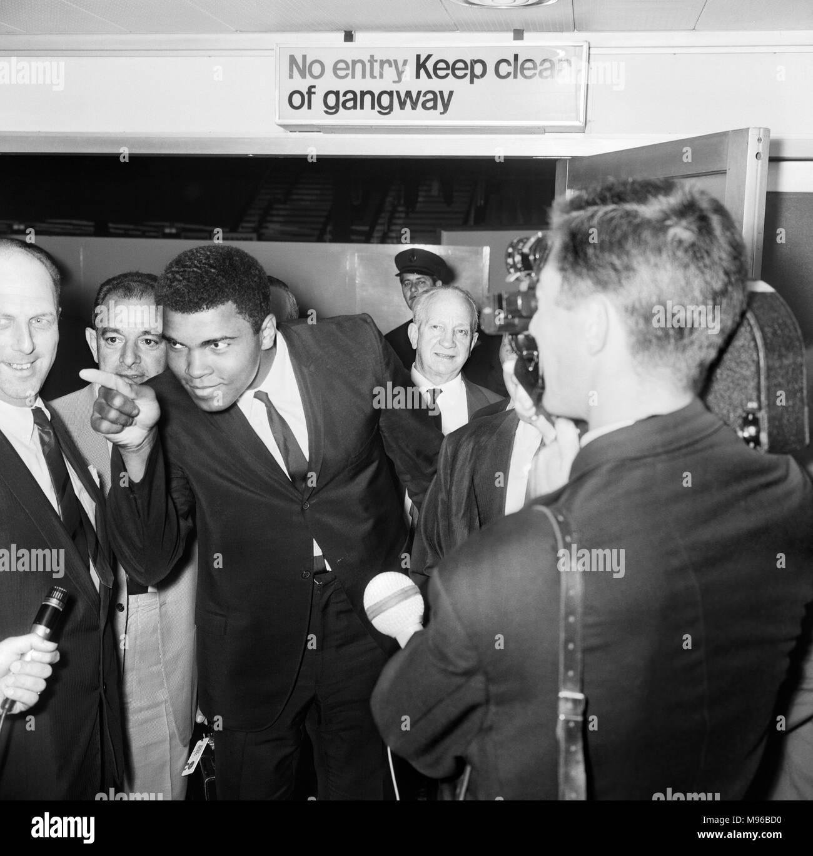 Muhammad Ali (nacido Cassius Marcellus Clay,) fue un boxeador profesional y Olímpico Estadounidense y activista. Él es ampliamente considerado como uno de los más importantes y célebres figuras del deporte del siglo XX. Desde muy temprano en su carrera, Ali era conocido como un inspirador, polémico y polarización figura tanto dentro como fuera del ring. (Foto) Mundo Campeón de Peso Pesado Cassius Clay (alias Muhammad Ali) en el aeropuerto de Heathrow. El 24 de julio de 1966 Foto de stock