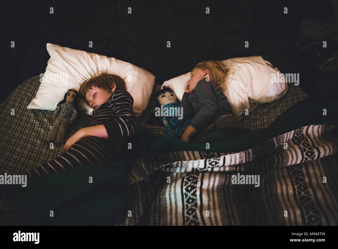 Dos niños con muñecas sentando en la cama Imagen De Stock