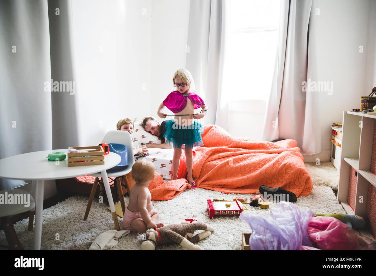 Chica en vestirse con la familia a su alrededor. Imagen De Stock
