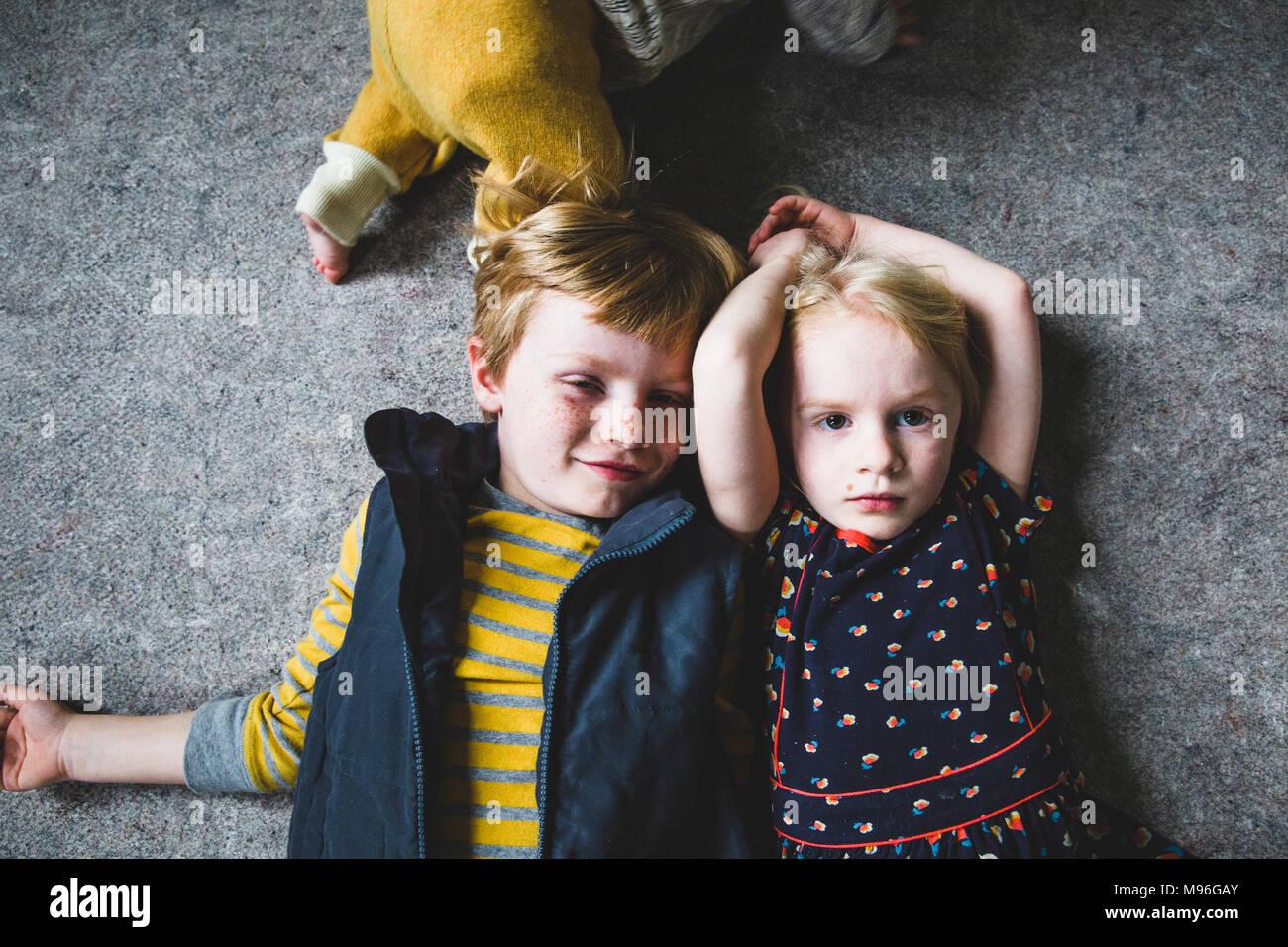 Hermano y hermana, poniendo uno al lado del otro Imagen De Stock