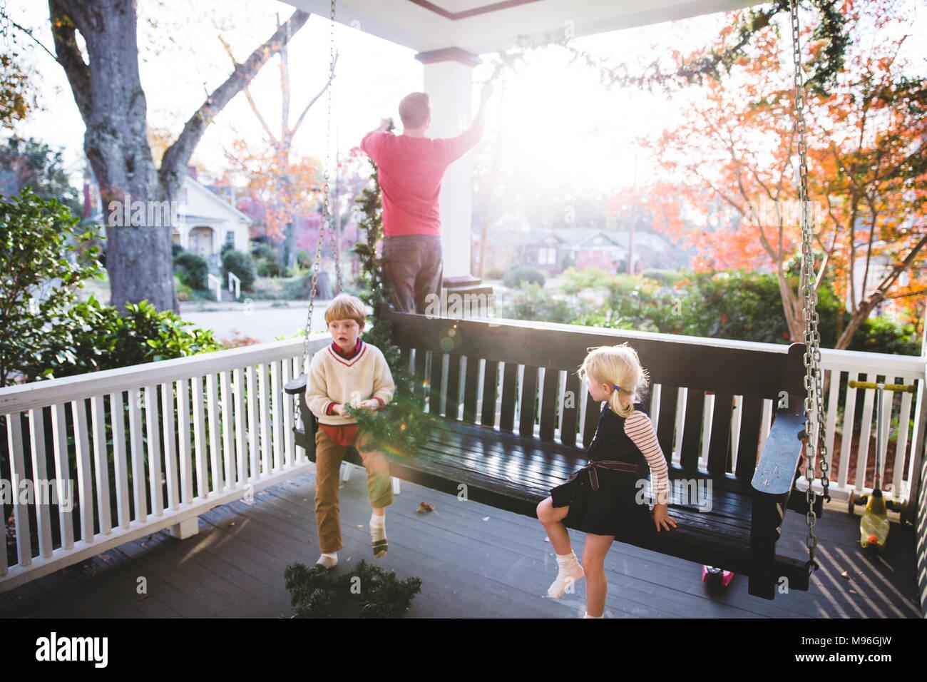 Los niños sentados en banco rítmico con el hombre en segundo plano. Imagen De Stock