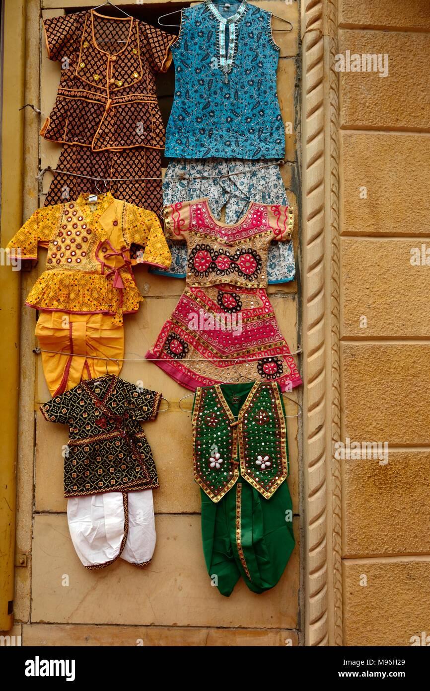 Ropa de niños indios tradicionales colgado en una pared de piedra arenisca amarilla en un mercado callejero de Jaisalmer India Ragashan Imagen De Stock