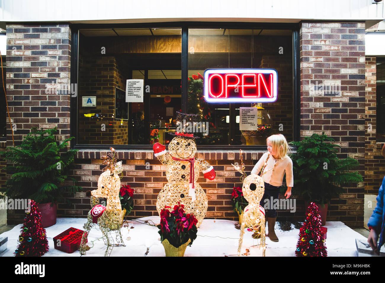 Chica con decoraciones de Navidad junto al restaurante abierto Imagen De Stock