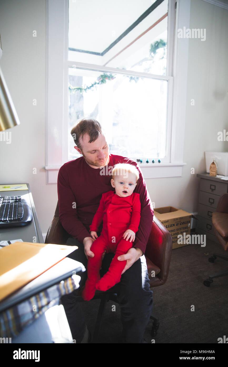 Padre celebración hija mientras trabaja desde casa Imagen De Stock