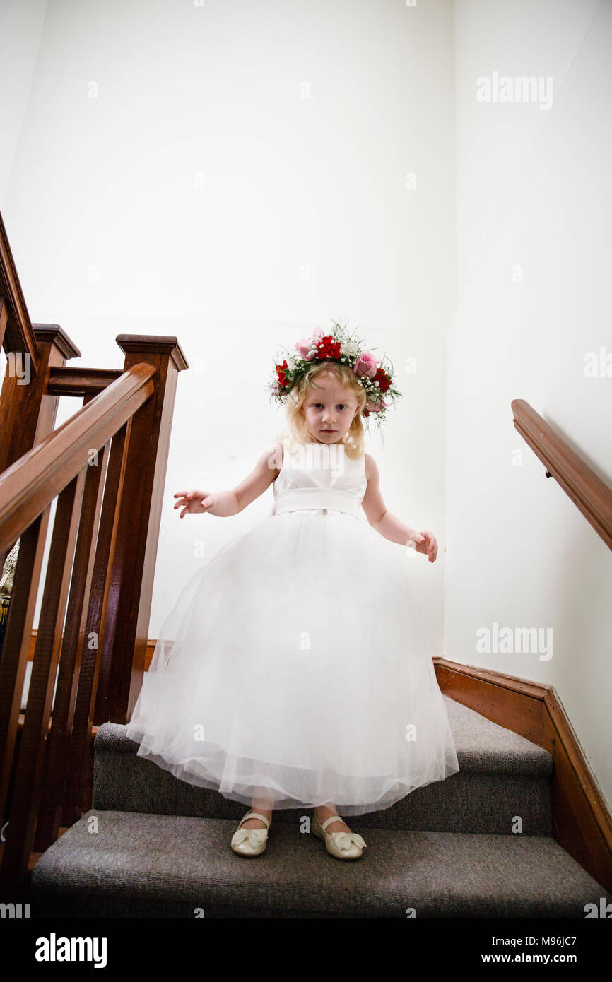 Chica en vestido blanco esperando en la parte superior de las escaleras Foto de stock