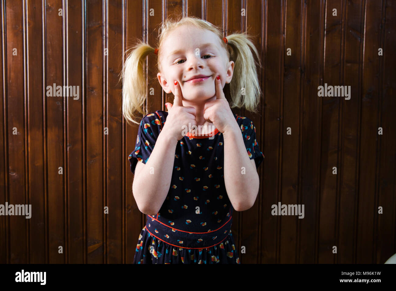 Chica con pigtails tirando de caras Imagen De Stock