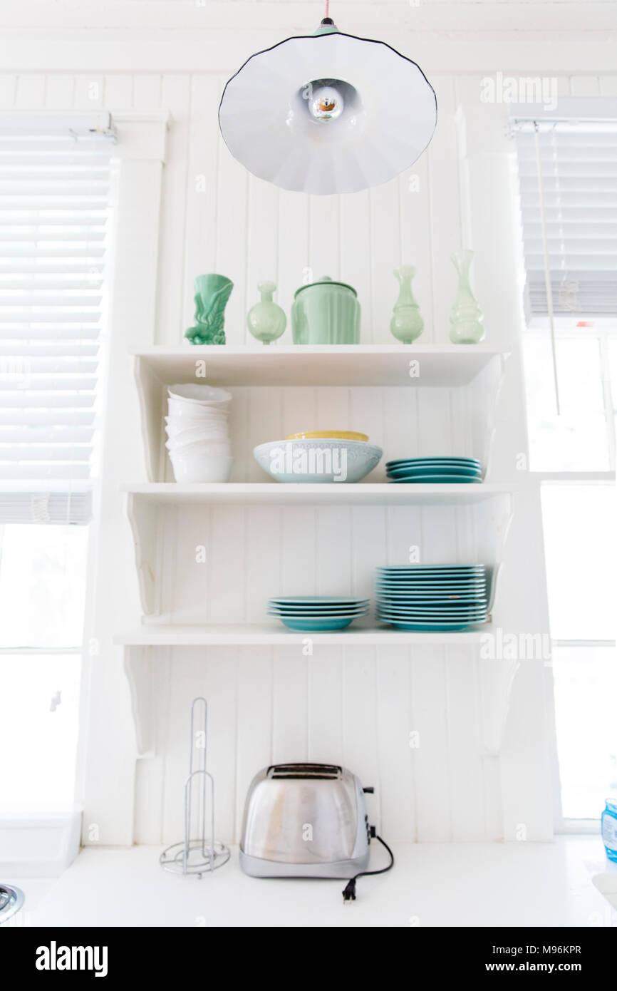 Estantes de cocina con platos, cuencos y tostadora Foto de stock