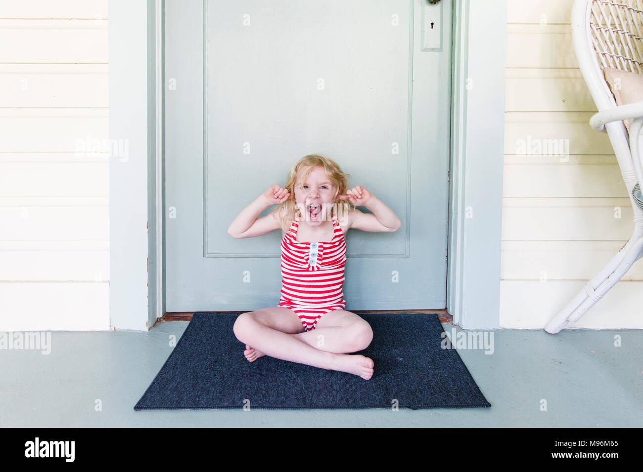 Chica tirando se enfrenta a la parte exterior de la puerta Imagen De Stock