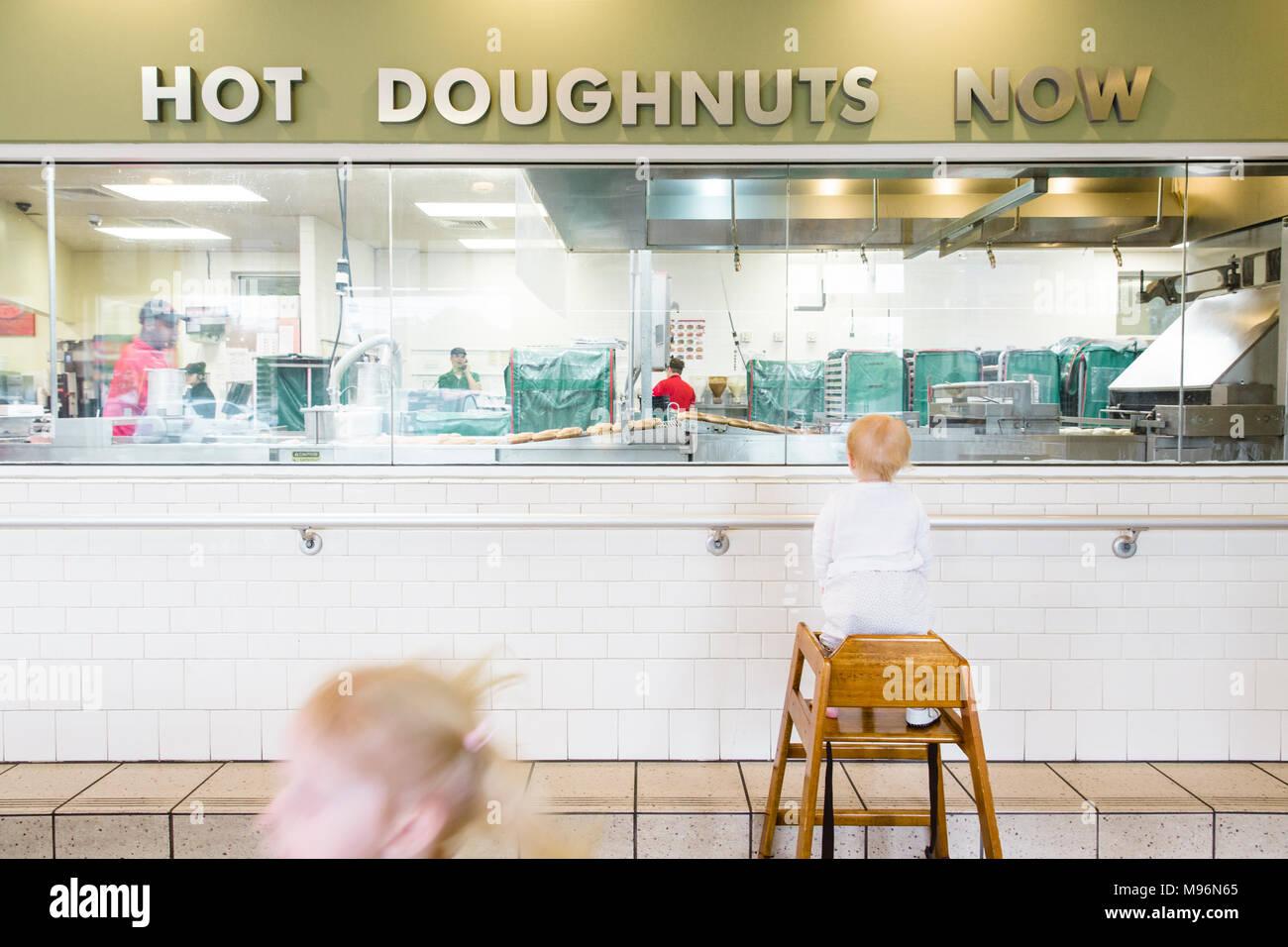 Niños mirando donuts están preparados Foto de stock