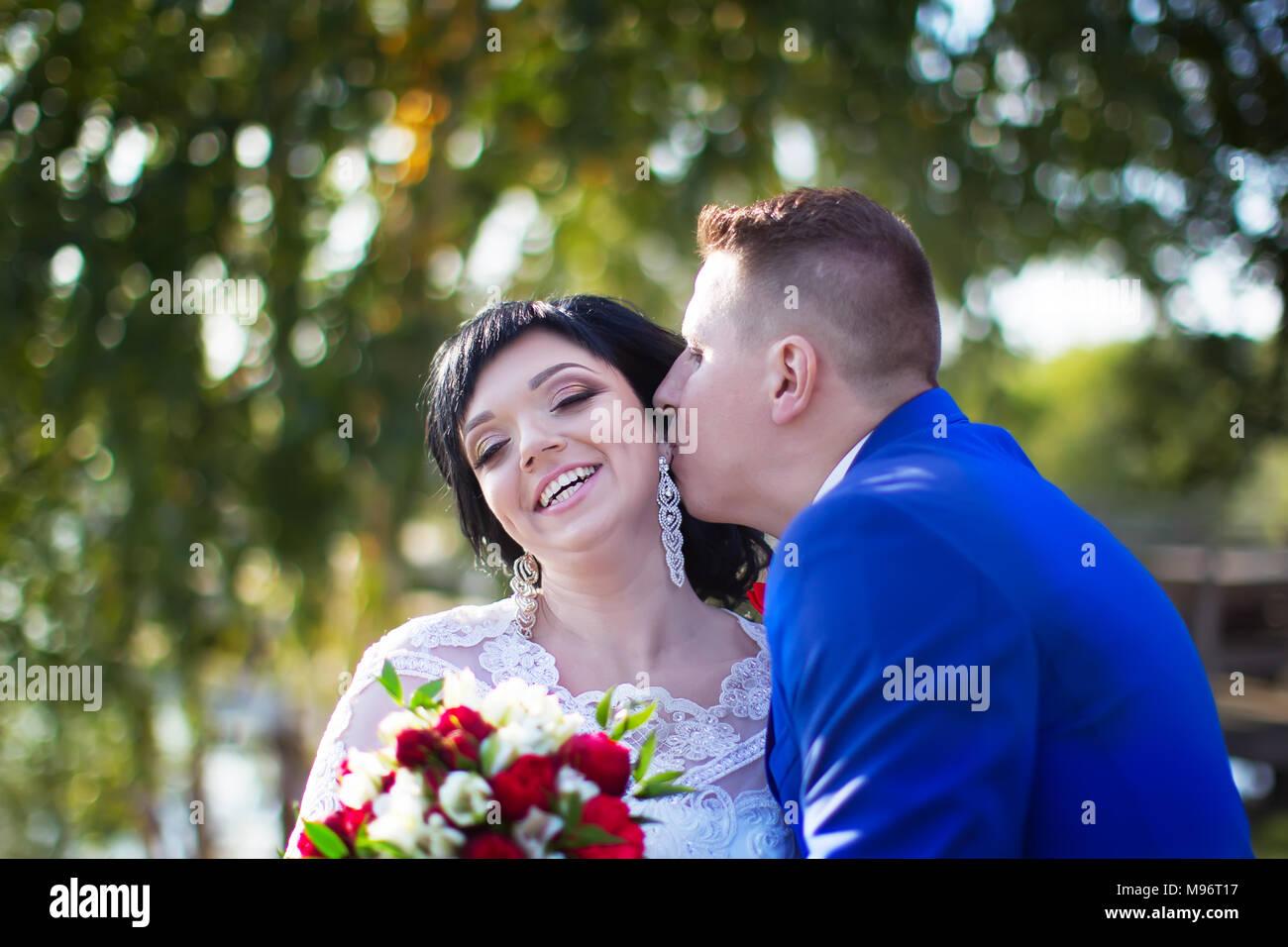 Belarús, Gomel, 29 de septiembre de 2017, Fiesta de Bodas.El novio es un kisser a la novia. La novia y el novio. Feliz novia y novio beso Imagen De Stock