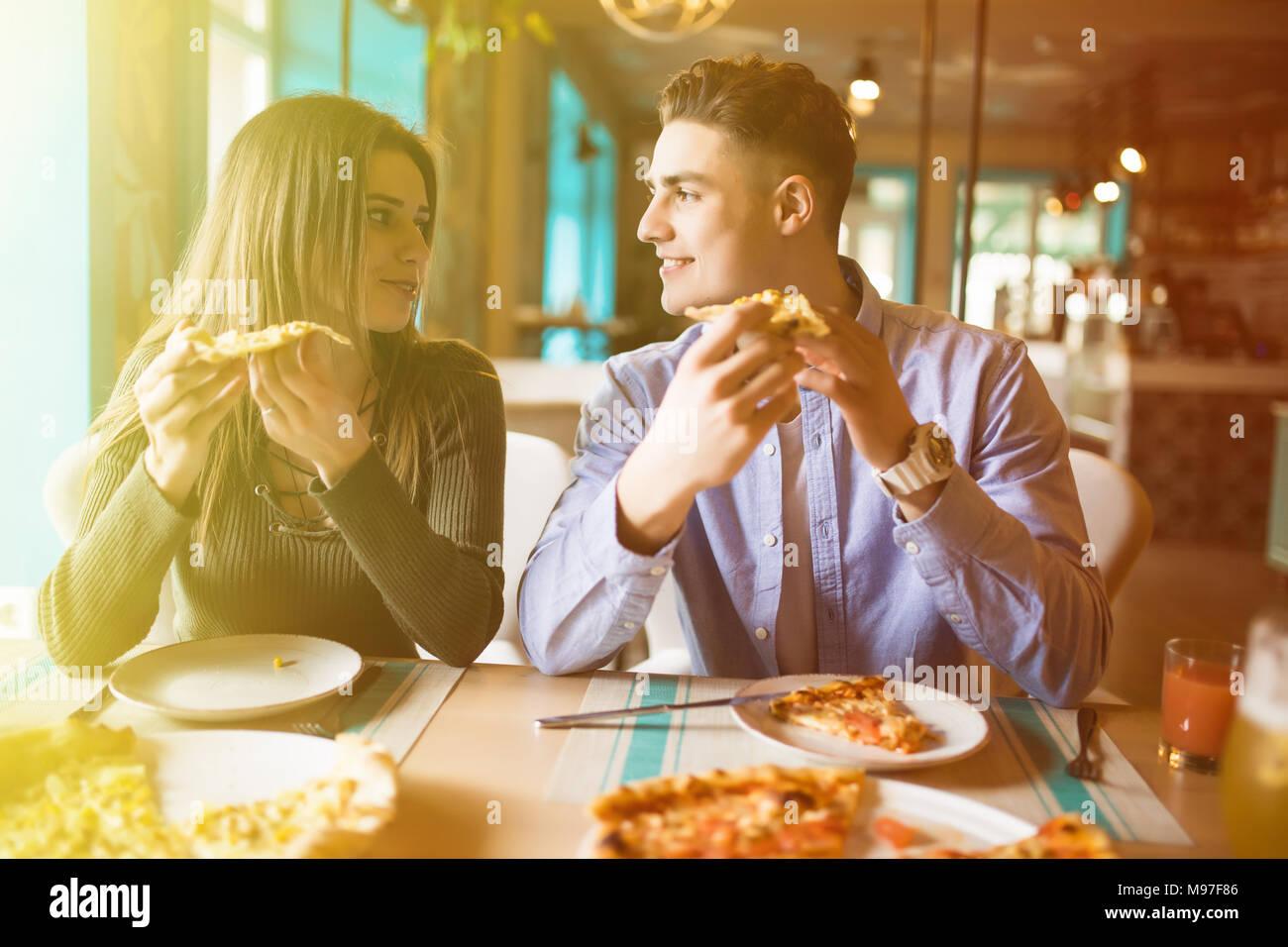 Cerrar foto de la joven pareja disfrutando en la pizza, divirtiéndonos juntos. El consumismo, la comida, el concepto de estilo de vida Imagen De Stock