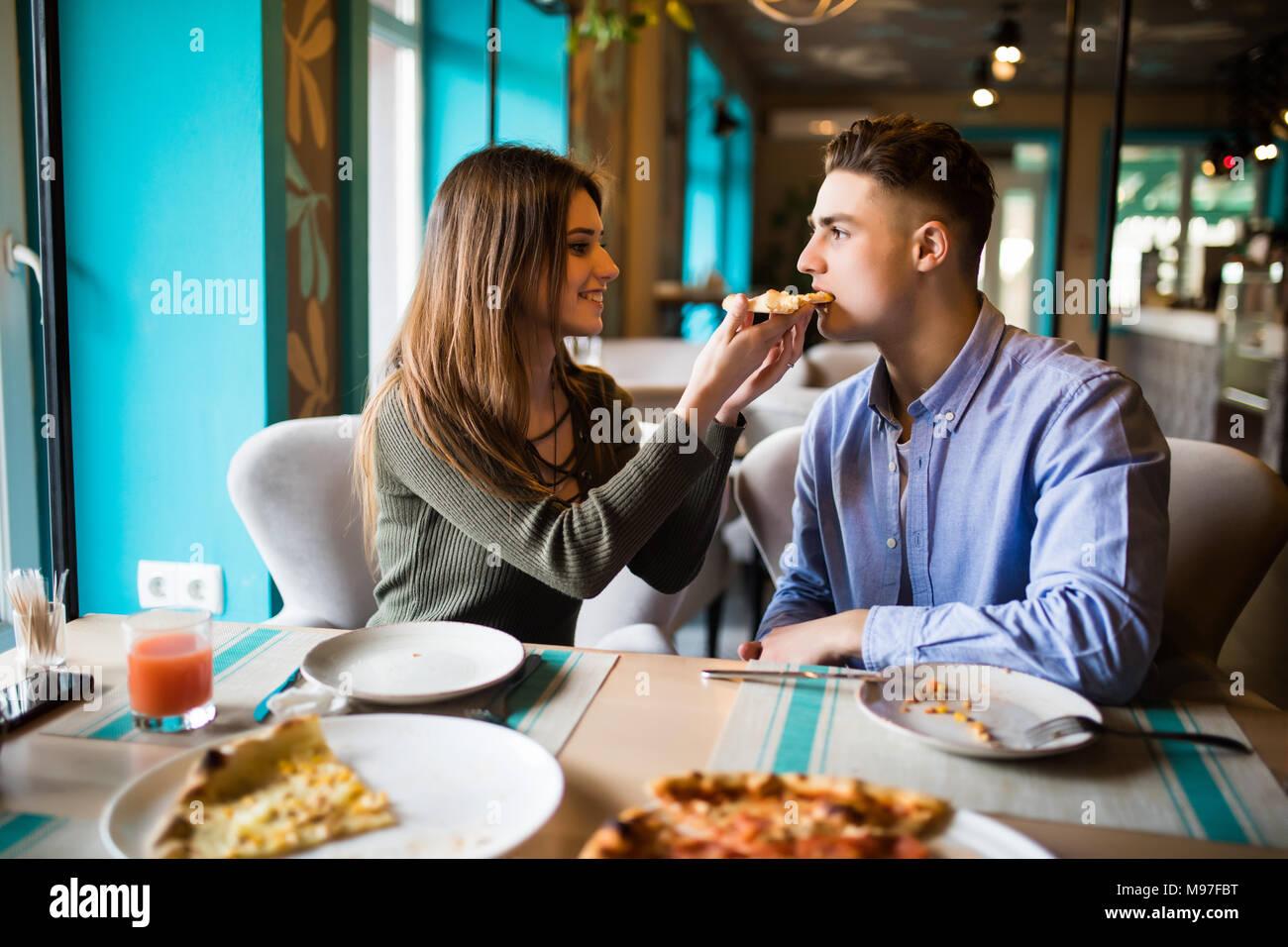 Citas en una pizzería. Guapo sonriente pareja disfrutando en la pizza, divirtiéndonos juntos. El consumismo, la comida, el concepto de estilo de vida Imagen De Stock