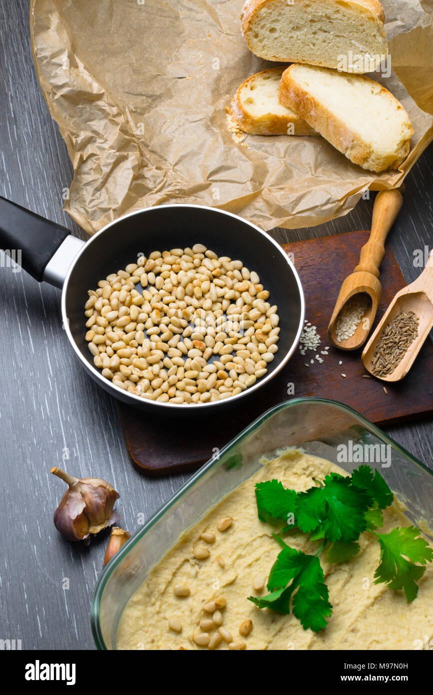 El hummus o houmous, aperitivo hecho de puré de garbanzos con tahini, limón, ajo, aceite de oliva, perejil, comino y tuercas en la mesa de madera de cedro. Estilo de vida saludable y comer bien concepto Imagen De Stock