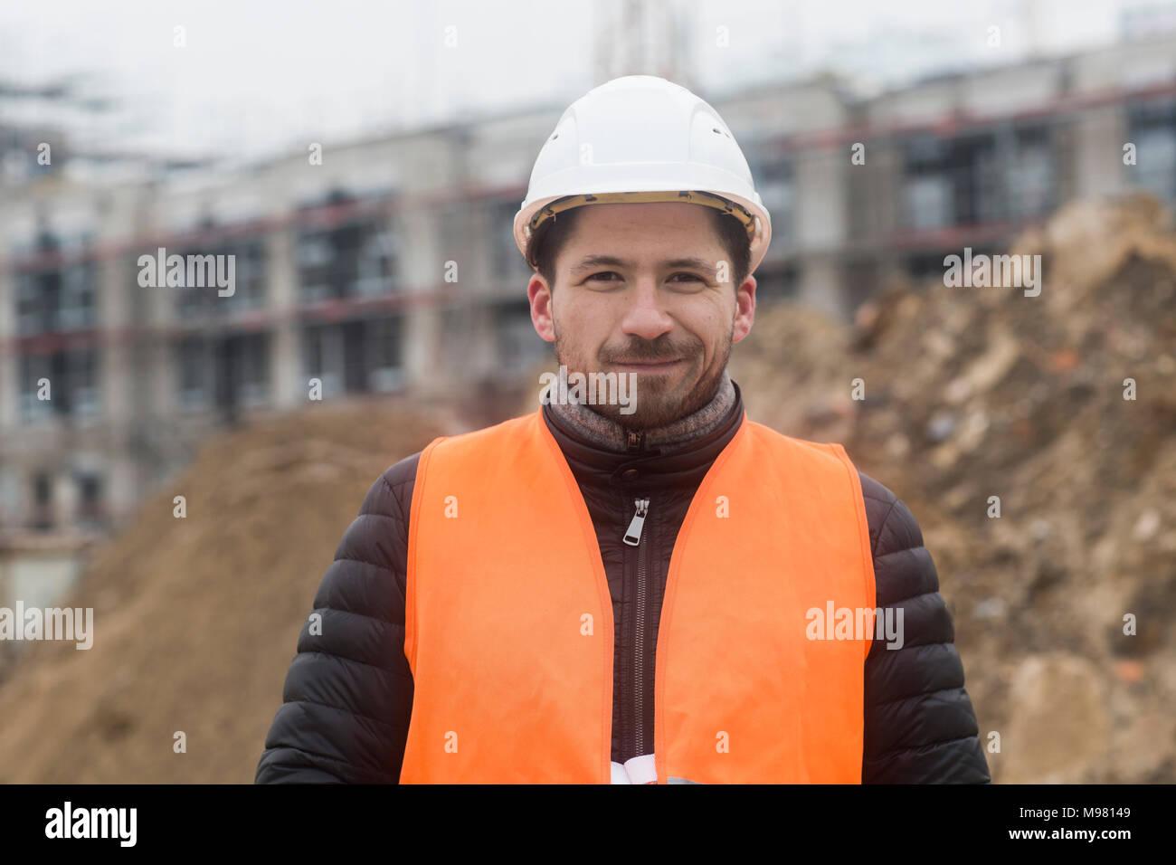 Retrato de contenido hombre vestido con chaleco de seguridad y el casco en el sitio de construcción Imagen De Stock