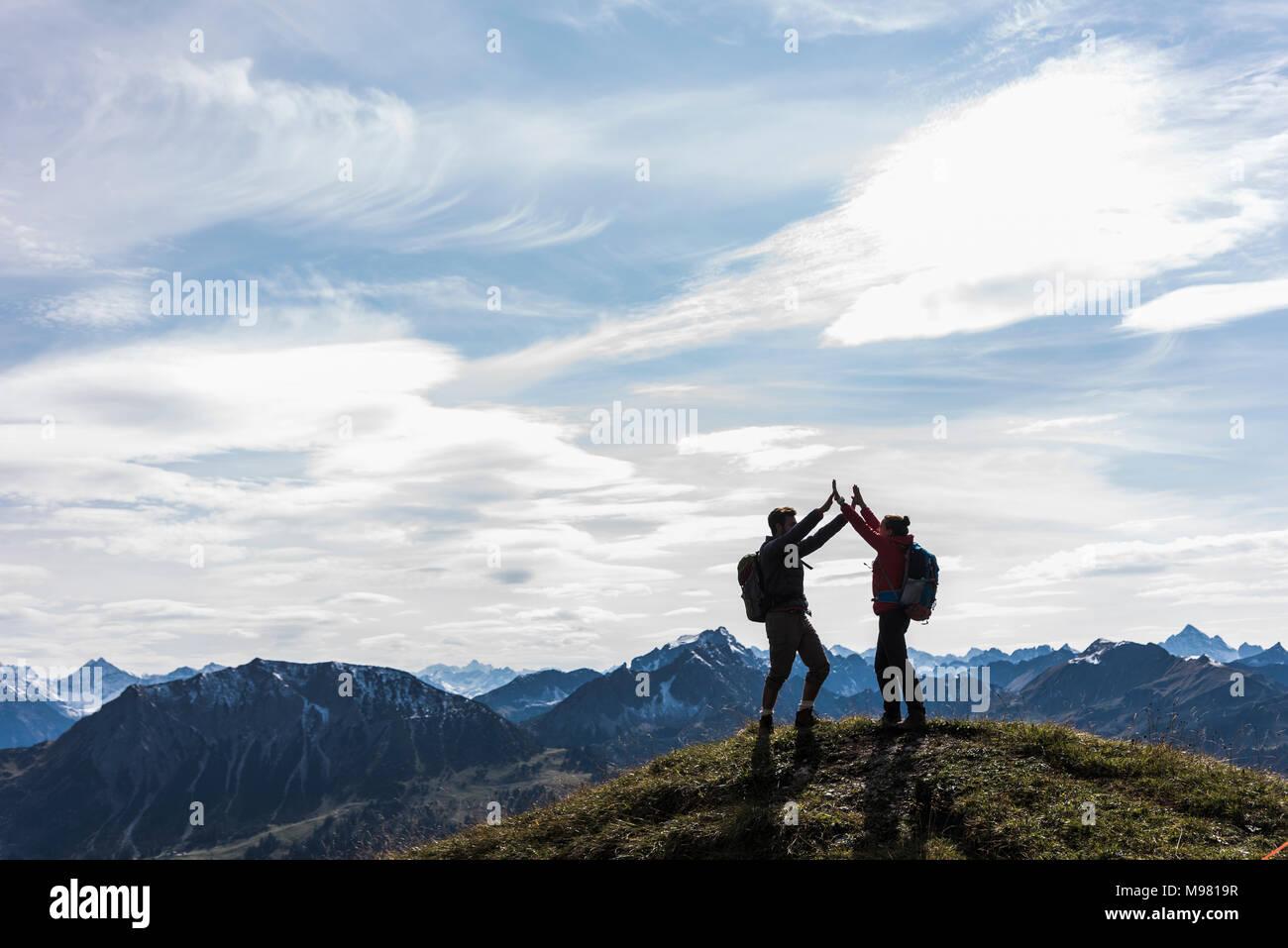 Austria, Tirol, pareja joven de pie en mountainscape vítores Imagen De Stock