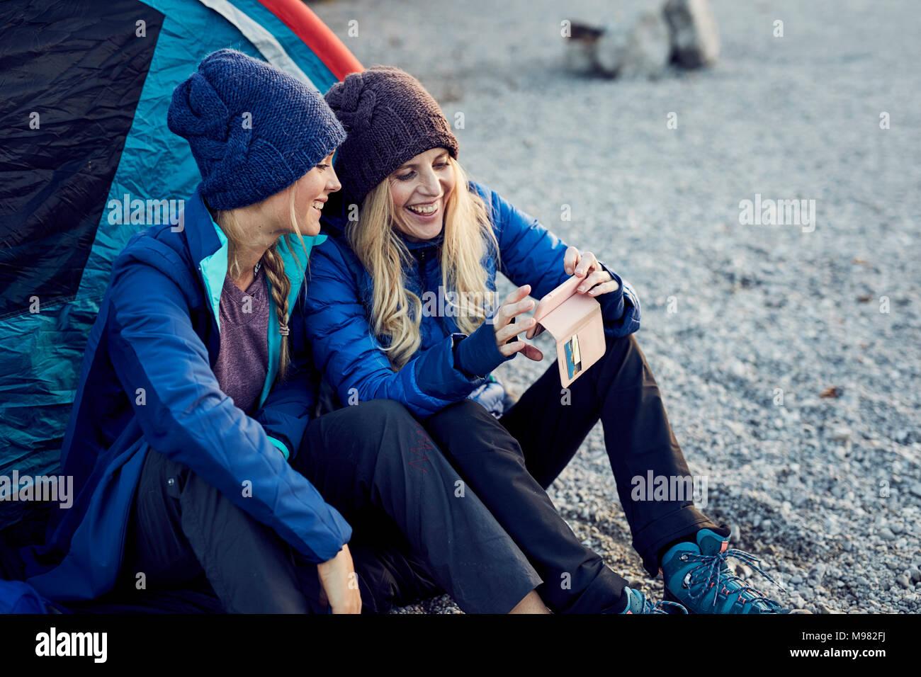 Dos amigas feliz sentado en carpa mirando teléfono celular Imagen De Stock