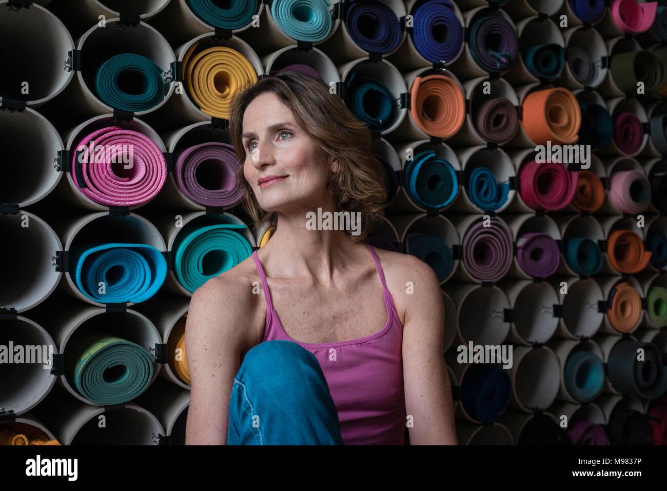 Sonriente mujer madura en frente del surtido de las esteras del yoga Foto de stock