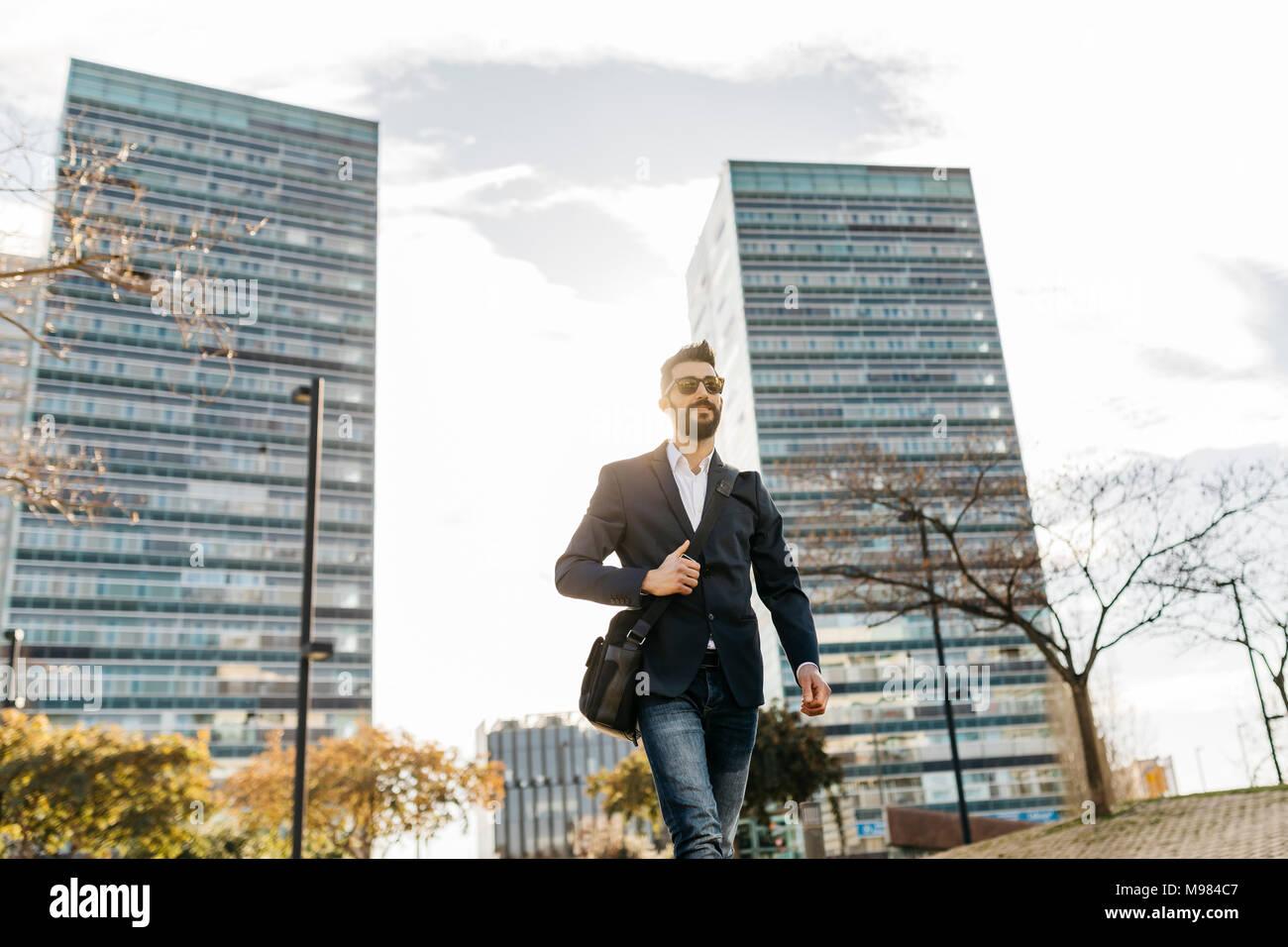 Empresario con gafas de sol caminando fuera del edificio de oficinas Imagen De Stock