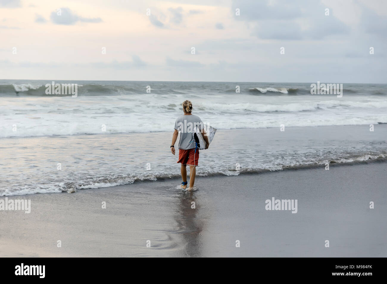 Indonesia, Bali, surfer caminar en el agua Foto de stock