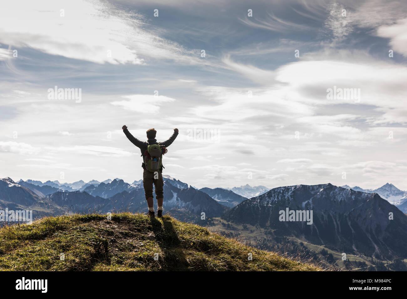 Austria, Tirol, joven parado en mountainscape vítores Imagen De Stock