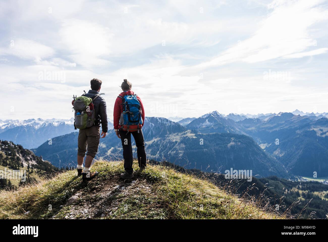 Austria, Tirol, pareja joven de pie en mountainscape mirando a ver Imagen De Stock