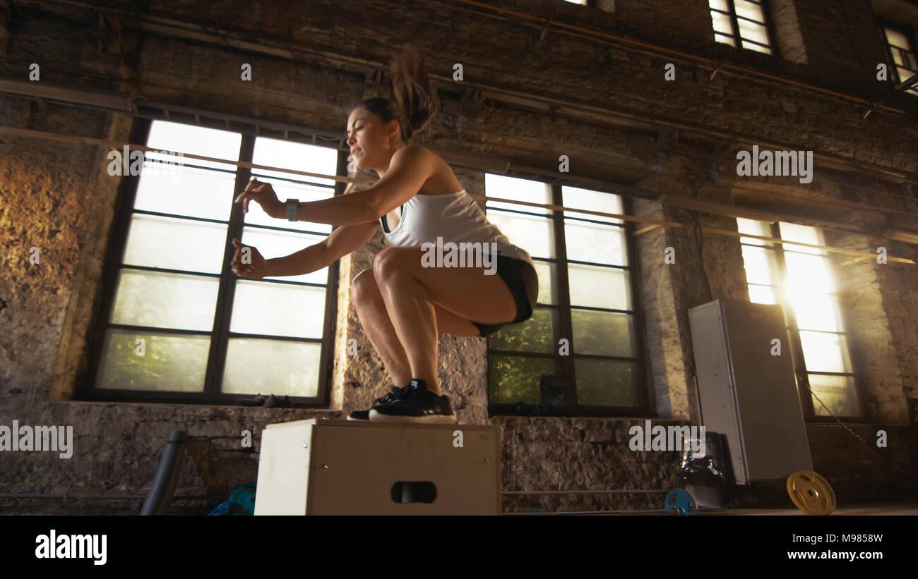 Colocar el Athletic mujer hace caja salta en la fábrica desierta gimnasio. El ejercicio intenso es parte de su programa de entrenamiento cruzan diariamente. Imagen De Stock