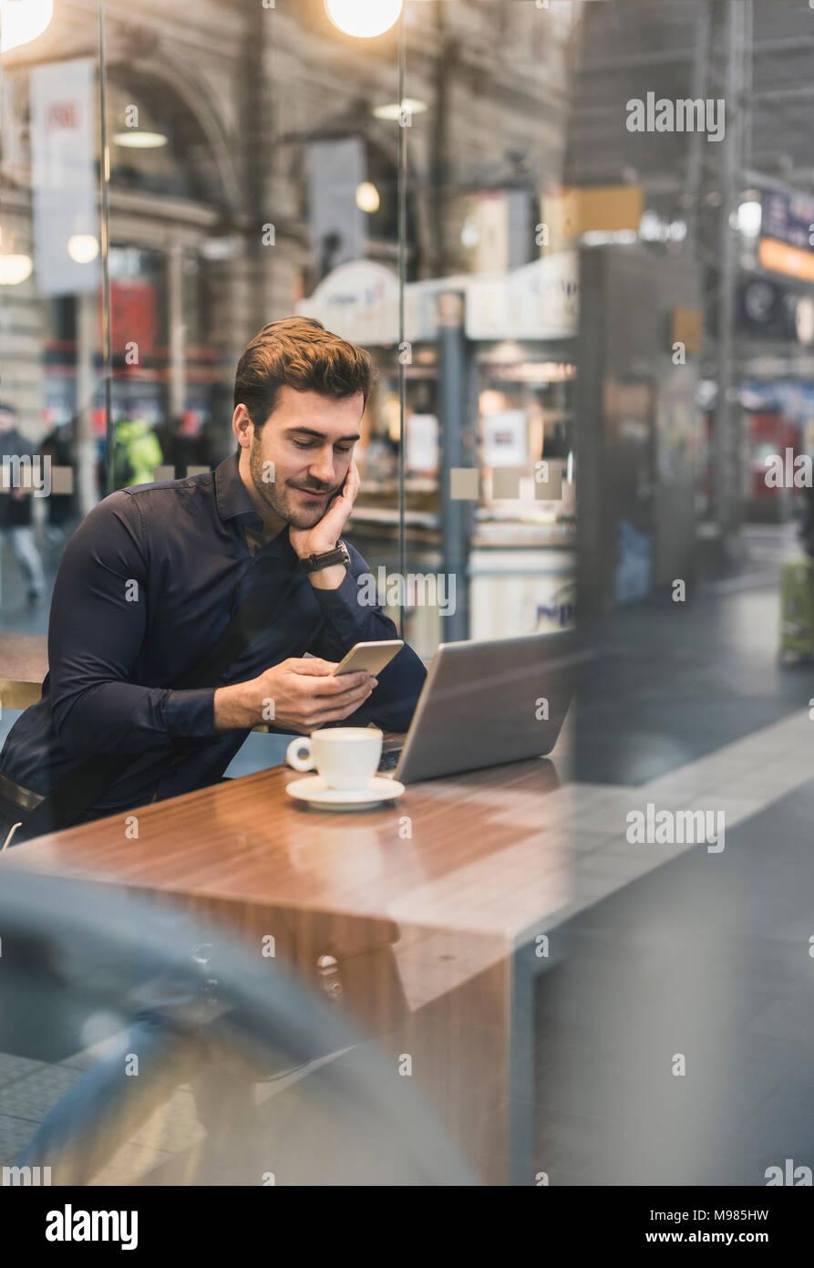 Empresario joven en un café en la estación de tren con teléfono móvil y portátil Imagen De Stock