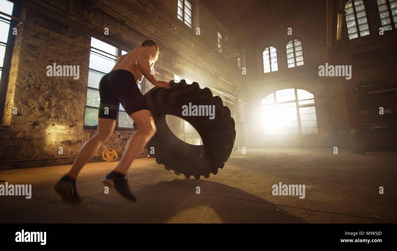 Hombre Fuerte musculatura ascensores neumático como parte de su programa de entrenamiento cruzado. Él es cubierto en sudor y trabaja en una fábrica abandonada remodelados en el gimnasio. Imagen De Stock