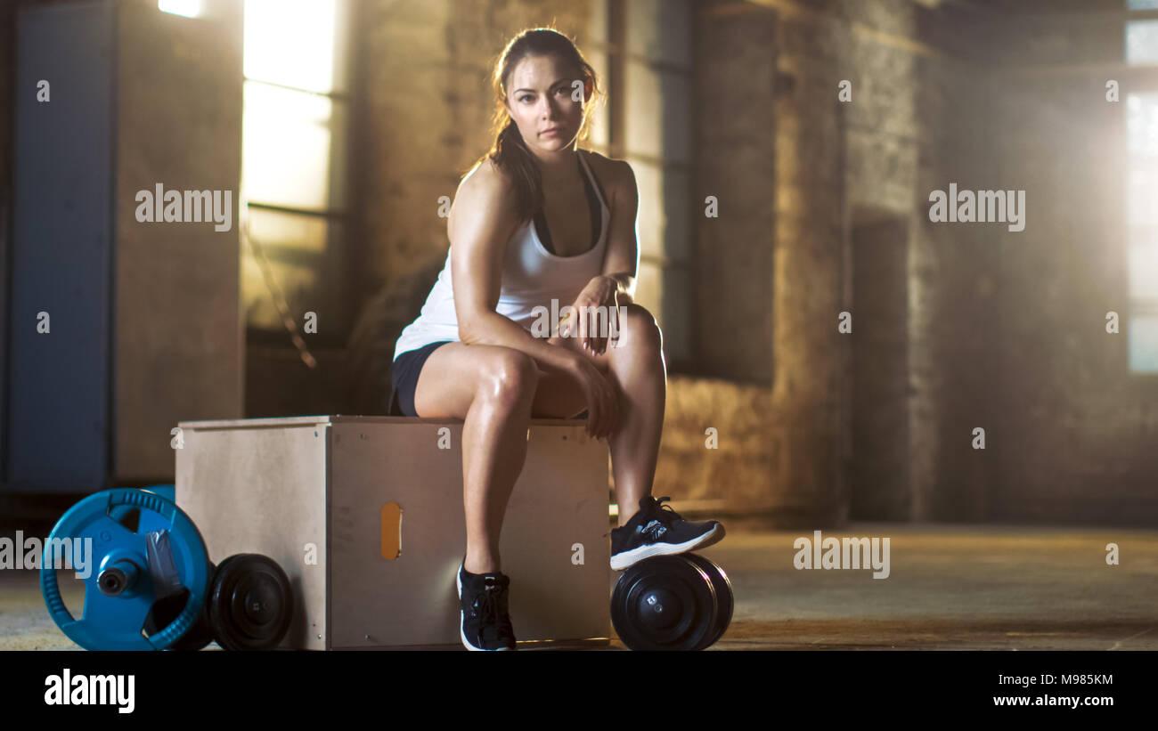 Hermosa Mujer atlética Smartphone utiliza para realizar un seguimiento de su intensa Cross fitness musculación programa de ejercicios en su gimnasio favorito. Imagen De Stock