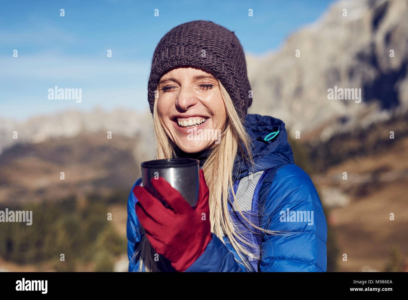 Retrato de mujer alegre y sosteniendo la taza en las montañas Imagen De Stock